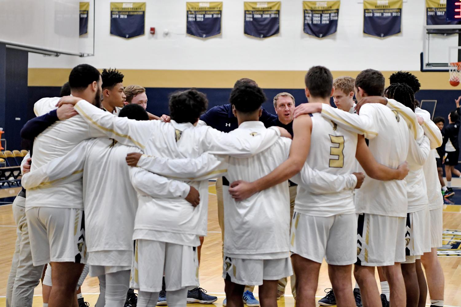 Boy's Varsity Basketball in a pre-game huddle.
